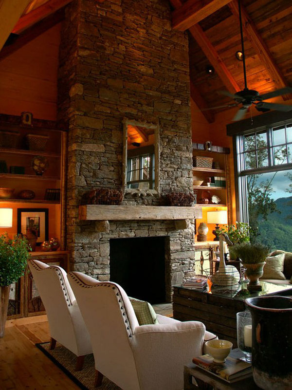Awesome Stone Fireplace Design For Cozy Living Room: Cool Tall Sloping Ceiling Villa With Amazing Tall Stone Fireplace Beetwen Bookshelves With White Leather Armchair Sofa And Natural Landscape View Tall Glass Window Ideas