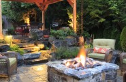 Inspiring Outside Flooring Ideas : Alderwood Landscape Traditional Patio Hardwood Floors Throughout And Dark Brown Trim Stones Fireplace And Grasses Around It