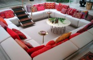 Awesome Indoor Pits Design : Amazing Rectangle Indoor Conversation Pit Design With Red Scheme Pillow With Unique Shape Round Glass Coffee Table And Small Wooden Staircase