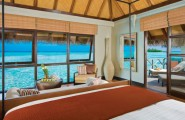 Breathtaking Beauty Remote Islands Resort: Four Seasons Resort Maldives : Astonishing On Water Bungalow Bedroom Interior Design With Large Glass Window And Blind Fold With Lounge On Wooden Flooring Terrace Ideas