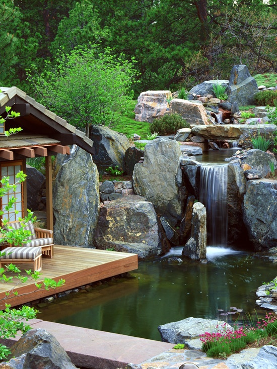 Stunning Relaxing Garden And Backyard Waterfalls : Beautiful And Tranquil Man Made Water Fall Huge Rock Bolders Close To Nature Simple Wooden Cottage Above The Pond Quiet And Secluded