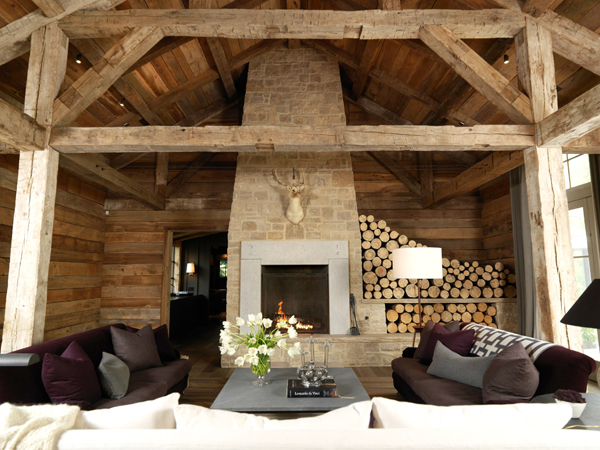 Sleek Stone Ornament for Modern Fireplace in Classic Villa: Beautiful Tall Rustic Fireplace With Chimney In An Exotic Living Room With Huge Exposed Wooden House Beams And Stacked Logs As Extra Accent