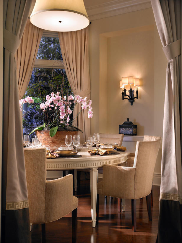 Perfect Chandelier For Your Dining Room : Beautiful Transitional Dining Room With Cream Round Dining Table That Contrast With The Dark Wood Flooring Dramatic Drapes Frame Sconces And Chandelier