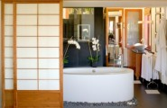Relaxing Japanese Bathroom Model For You Apartment : Black Granite Japanese Bathroom With Oval Bathtub Surrounded By Stone Pebbles Wooden Sliding Door