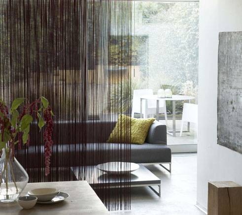 5 Sliding Panel Window Treatments That Acts as Room Dividers Too : Bounded Family Room With Sliding Panels Of Patterned Fabric With Leather Length Buckwheat Small Table In Front Of A Simple White Background With Large Window