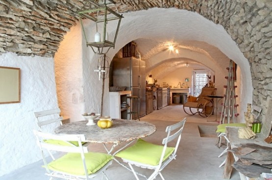 Unique Stone House: Charming Unique House With A Living Room With A Round Wooden Table And Dining Chairs Green With Exposed Stone Walls With Unique Pendant And A Cross Underneath