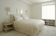 Sophisticated Design In Modern Home : Comfortable Calm Tone Soft Bed In An All White Serene Bedroom With A Large Fur Carpet And Simple Furniture