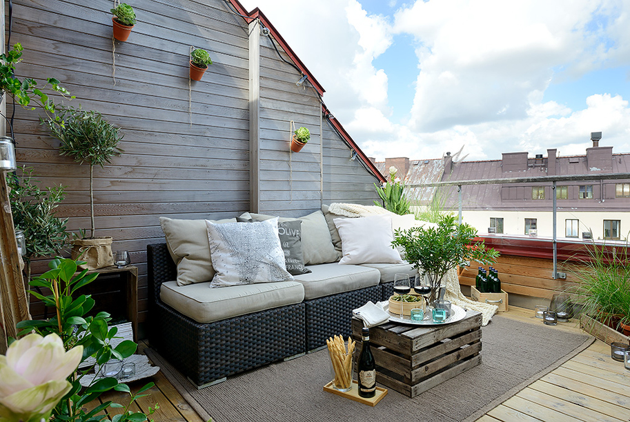 90sqm Elegance And Minimalism Apartment Design In Swedish : Cool Outdoor Terrace Design With Rattan Sofa Cushion Wooden Wall Unique Table Box Plants Rug Glass Fence Wooden Flooring Ideas