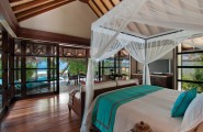 Breathtaking Beauty Remote Islands Resort: Four Seasons Resort Maldives : Cozy 4 Season Resort Beach Bungalow Wooden Flooring And Large Glass Sliding Door Bedroom Interior Design With Mosquito Net And Sea View Sofa Ideas