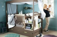Cozy And Cheerful Modern Nursery Room Design : Cozy Light Blue Nursery Room Interior Design With Chocolate Baby Cribs Integrated With Shelves And Hidden Extra Bed With Netting Blanket And Small Round Rug On Wooden Flooring Ideas