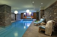 Modern swimming pool designs : Inspiring Amazing Poolside Area Designs Indoor With Simple Chair And Table Using Wonderful Stone Wall
