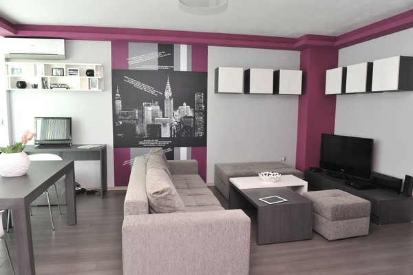 Small Apartment Design And Decoration: Inspiring Purple Accent Living Room In Small Apartment With Dark Grey Desk Grey Sofa Black White Hanging Wall Cabinet Hanging Shelves Square Grey Living Table Laminated Flooring