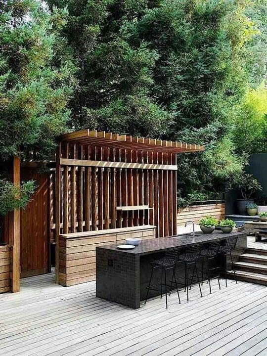 Coziest Space For Outdoor Kitchen Designs Near The House: Interesting Outdoor Kitchen Decoration With Nice Pergola Black Marble Glass Top Dining Table And Wooden Pantry Floor Design