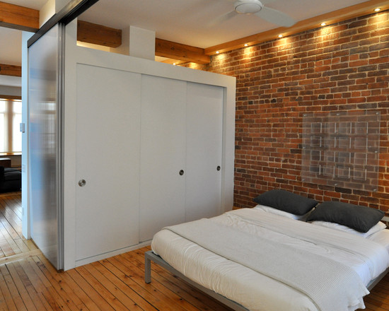 Free Standing Closet For Various Functions: Modern Bedroom With Free Standing White Closet Bed Frame In The Middle Of The Room Brick Exposed Wall With Down Lighting
