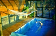 Various Indoor Swimming Pool Design Ideas : Outstanding High End Indoor Endless Swimming Pool With Water Propulsion System Combined Wood With Hammock And Large Glass Window