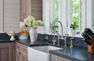 Exciting Farm Sink With Delta Bridge Faucet : Rustic Kitchen With Wood Walls And Cabinets Farmhouse Sink Faucets Soapstone Countertops Casement Windows In Front Of Extended Sink Area