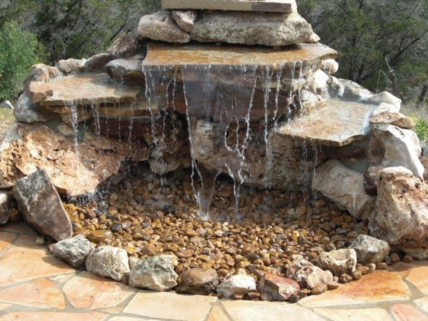 Stunning Relaxing Garden And Backyard Waterfalls: Small Man Made Water Fall Design With Flat Stones Stacked Together To Create Illusion Of A Small Cliff Where The Water Falls Into A Bed Of Pebbles ~ stevenwardhair.com Design & Decorating Inspiration