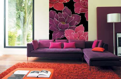 Bold Sunny House With Cozy Living Room: Spacy Bright Colorful Living Room Design With A Large Print Picture Wall Simple Purple Sofa And Cool Lamp Design With Red Fur Rug