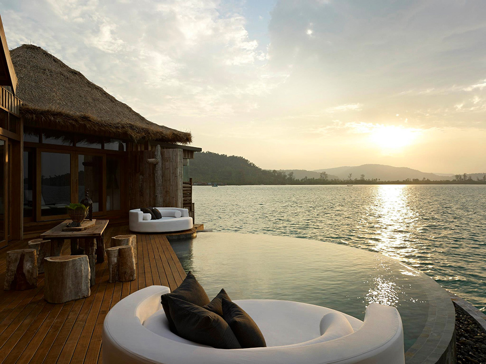 Song Saa : Private Remote Island Resorts In Cambodia: The Ultimate Luxury Experience At Sunset On Overwater Villa Deck Exterior Design With Solid Wood Table Set And Lounge Cushions And Private Infinity Pool