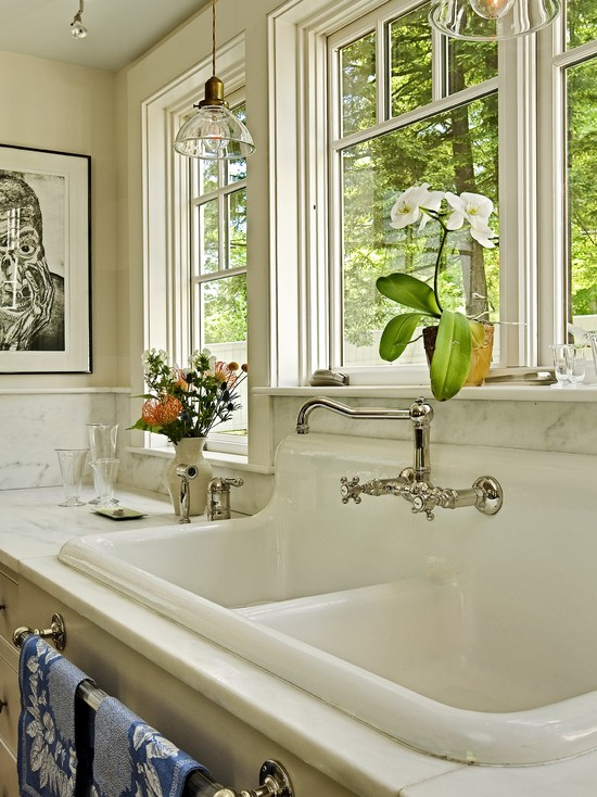Exciting Farm Sink With Delta Bridge Faucet: Traditional Kitchen Sink And Faucet With A Dark Paneled Cluttered Divided Space With Little Natural