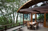 Unusual Wild Nature and Cool Modern Home Designs on Tropical Forest : Wild Nature And Cool Modern Home Patio Designs With Wooden Table 8 Wooden Chairs Wooden Balcony Floor Glasses Sliding Door Large Glasses Windowr Round Roof