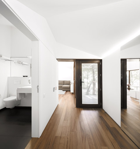 Creative Hut With Modern Style: A White Bathroom With Polished Black Floor In A Natural Sustainable Hut