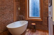 Trendy Freestanding Bathtubs Designs For Luxurious Bath : Amazing Exposed Brick Wall And Warm Wooden Floor Complement The Modern Bathtub Elegantly