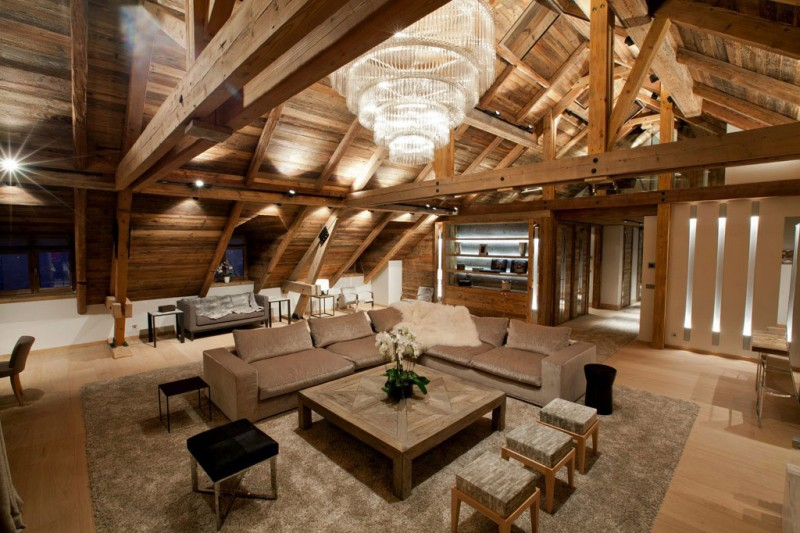 Modern Rustic Apartment With Visible Wooden Support: Incredible Crystal Chandelier Installed On Iced Winter Home Attic Ceiling Above Square Wooden Table In Living Room