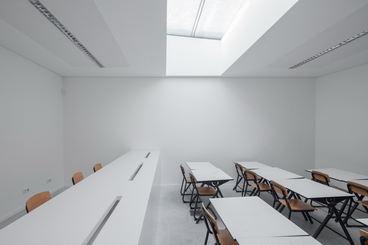 Oval Private College Design With Unique Architecture : Minimalist White Classroom With White Table And Brown Chairs