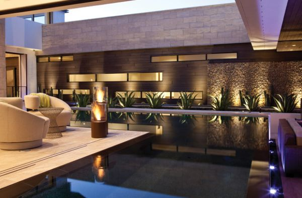 Stunning Outdoor Fireplace Design In Various Styles: Modern Lighthouse Fireplace Next To The Outdoor Pool And Patio ~ stevenwardhair.com Fireplace Inspiration