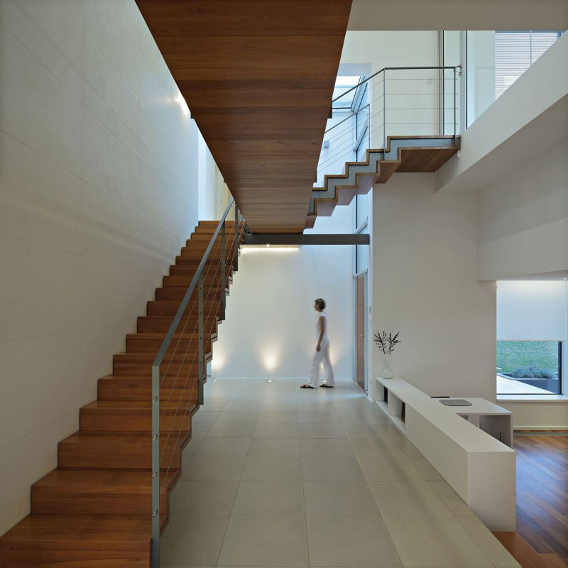 Simple Modern Home And Indoor Lap Pool: Open J20 House Hallway And Entryway Area Showing Wooden Staircase And Low Cabinetry Set As Room Divider
