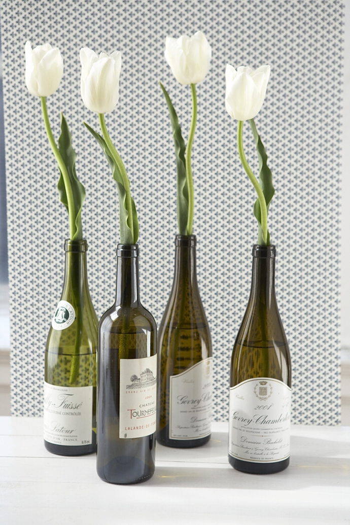 Sparkling Wine Bottle In Eco Friendly Theme For Recycling: Sensational Wine Bottle As Vase For Beautiful White Flowers On The White Table Near Grey Wall